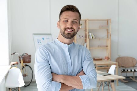 Portrait of smiling young Caucasian male employee leader or CEO posing in modern office, happy confident millennial European man boss look at camera show motivation and leadership at work