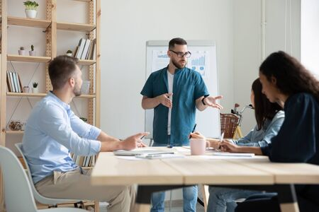Concentrated Caucasian male leader in glasses stand lead meeting with diverse colleagues, focused confident young boss head briefing with coworkers in office, cooperation, teamwork concept Stock fotó