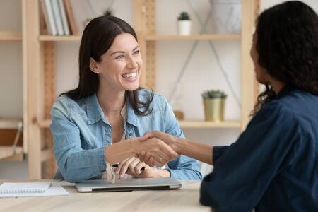 Smiling female recruiter or employer shake hand greeting get acquainted with job candidate at interview in office, happy woman boss handshake business partner or client at meeting, employment concept Stockfoto