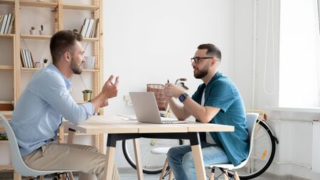 Young male employer or boss sit at desk talk with job candidate in modern office, concentrated ceo or recruiter interview man work applicant, discuss cooperation at meeting, recruitment concept
