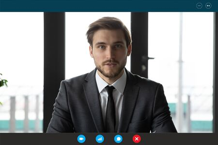 Headshot portrait screen application view of young businessman talk on video call with business client online, millennial male employee worker engaged in webcam briefing conference in office