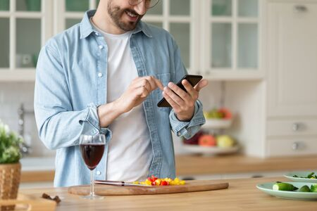 Smiling man using smartphone, reading vegetarian snack recipe online close up, looking at phone screen, happy young male cooking salad, preparing fresh vegetables in modern kitchen, healthy food