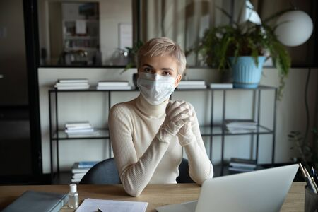 Pleasant successful responsible businesswoman in breath protective face mask and medical gloves sitting alone at modern workplace with computer or working remotely from home, looking at camera. 版權商用圖片