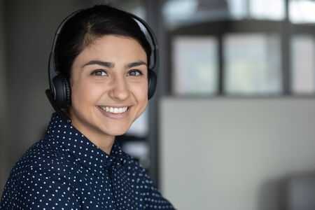 Head shot close up smiling attractive indian ethnicity millennial businesswoman wearing headphones, looking at camera. Happy sincere pleasant young mixed race female professional working remotely.