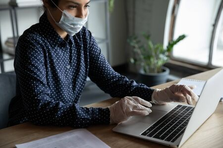 Cropped image millennial indian ethnicity businesswoman entrepreneur employee worker working on computer in protective gloves and medical facemask, adhering to security covid 19 quarantine measures.