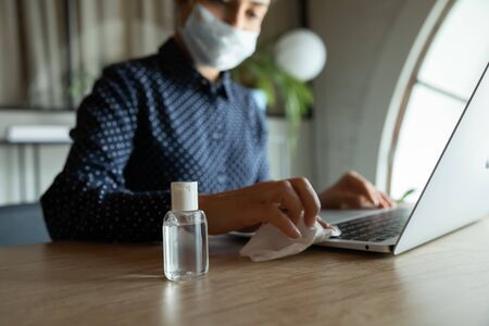Focus on plastic bottle with antiseptic alcohol-based liquid standing on work desk with cautious woman in medical facemask sanitizing computer keyboard on background, stop spreading virus infection.