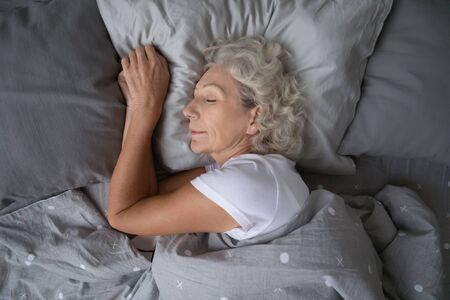 Above top view calm peaceful elderly mature hoary woman sleeping on soft pillow under blanket, enjoying sweet dreams at night. Happy middle aged granny lying on side, resting in comfortable bed alone.