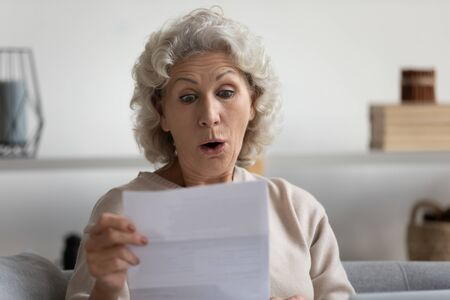 Head shot surprised middle aged mature woman looking at paper letter, reading unbelievable news notification, sitting alone on sofa at home. Stressed older grandmother received bank account balance.