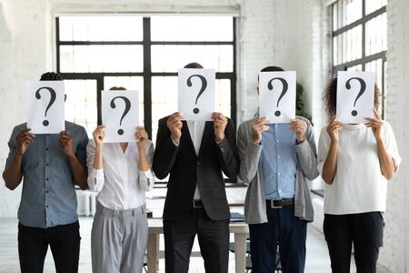 Diverse business people hiding faces behind papers sheets with question marks, standing in row in office. Identity and equality employee at work, candidates waiting for job interview, recruitment. Reklamní fotografie