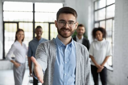 Close up headshot portrait of happy businessman shaking hand posture. Different smiling ethnicity businesspeople standing behind of male company chief. Leader of multi-ethnic team concept. Stock fotó