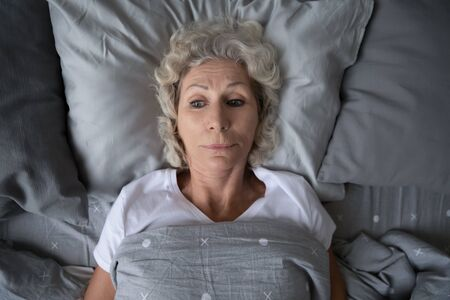 Head shot top above view stressed middle aged retired woman lying in bed under duvet with opened eyes, having problems with sleep. Unhappy mature old grandmother suffering from insomnia at night.