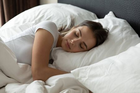 Calm millennial girl sleep peacefully on white fluffy pillow in cozy bedroom at home or hotel bedroom, happy young woman take nap daydream relax in comfy bed see dreams, relaxation concept