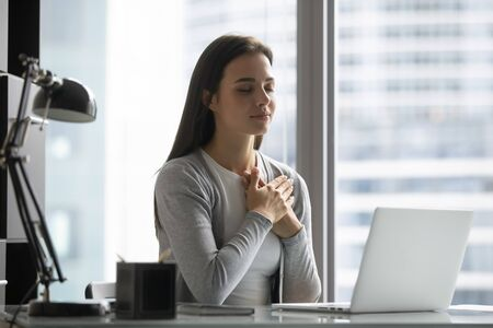 Peaceful young woman worker sit at workplace hold hands at heart chest feel grateful thankful for good luck or fate, millennial female employee believer meditate pray at desk in office, faith concept Stock Photo