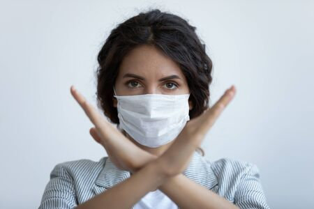 Head shot close up serious responsible young woman wearing breath protection facial mask, showing crossed arms stop sign, isolated on blue studio background, stay at home virus quarantine concept.