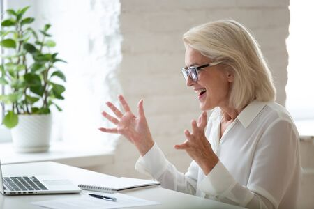 Excited 60 years old businesswoman celebrating business success achievement. Happy employee feeling motivated by good work, get job or promotion, receive great news in email, positive exam results.
