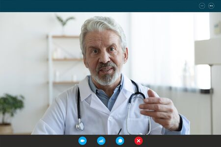 Ask general practitioner online, video call consultation, patient and doctor talk concept. Head shot of mature male therapist share information provide support, laptop screen view, videoconference app Stock Photo