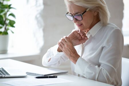 Unhappy 60 years old businesswoman holding wrist close up, suffering from strong pain in hand. Exhausted stressful employee feeling unwell in tired arm muscles, chronic health problem concept.