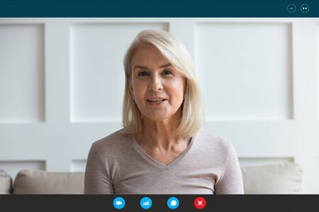 Head shot aged woman qualified psychologist looks at cam during psychological support session on-line counselling with client over telecommunication app. Chat via teleconference with relatives concept