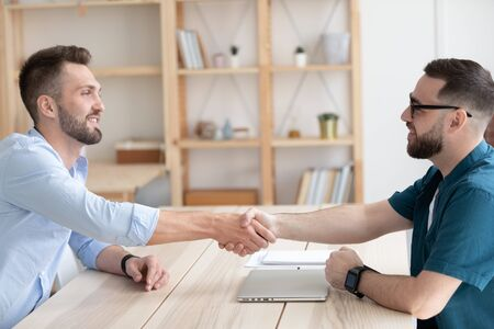Smiling male business partners shake hands greeting or get acquainted at office meeting, man employer or boss handshake job applicant congratulate with employment, good interview, recruitment concept Stockfoto