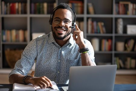 Happy young friendly african american man in eyeglasses wearing headset with mic, looking at camera. Smiling professional financial advisor consulting clients online, solving problems issues.