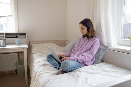 Teenage girl sitting on bed wearing headphones using laptop. Teen kid school student studying doing homework online, elearning in education app on computer website, browsing internet at home alone.