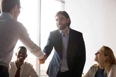Smiling Caucasian male colleagues shake hands get acquainted greeting at team meeting in office, happy businessmen handshake close deal make agreement after successful briefing, collaboration concept