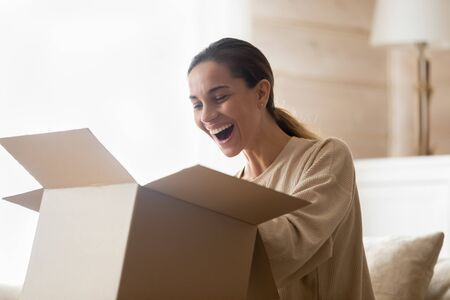 Excited young woman unpacking huge carton box, looking inside. Happy millennial female client satisfied with ordered purchase. Emotional lady surprised by fast delivery service, online shopping.