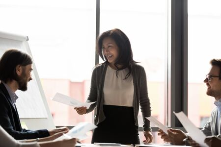 Smiling middle-aged Asian team leader female boss stand lead office meeting with diverse colleagues share financial documents handouts, happy ethnic businesswoman head group briefing with coworkers