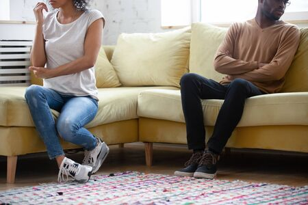 Cropped close up African American family ignoring each other, wife and husband sitting separately on sofa at home, unhappy girlfriend and boyfriend not talking after quarrel, break up or divorce