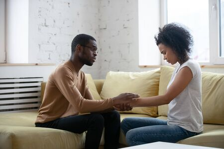 Care african american man comforting upset depressed woman holding wife hand for supporting frustrated disappointed girlfriend having life problem, showing love and support.