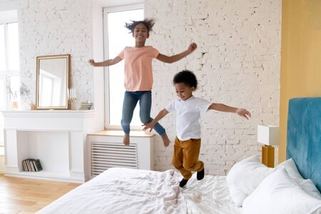 Happy african american children jumping at bedroom. Smiling and laugh diverse siblings enjoying weekend together at living room. Successful mortgage, cute kids on bed at new warm house. Standard-Bild
