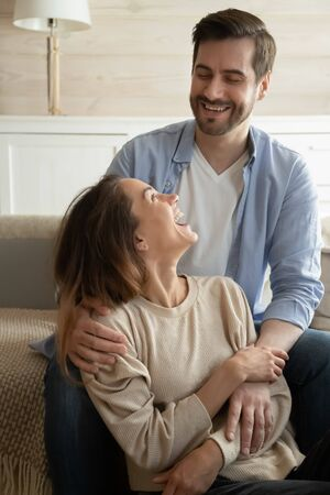Vertical image young bearded guy cuddling laughing girlfriend, enjoying fun time together at home. emotional positive energetic family couple joking talking chatting communicating with each other.