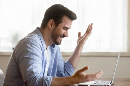 Side view excited young man looking at laptop screen, reading email with unbelievable good news. Cheerful bearded guy amazed by good job results, online lottery win, sitting at table at home.