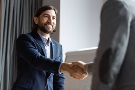 Smiling middle-aged businessman shake hand get acquainted greeting with male colleague at briefing, happy male employer handshake close deal make agreement at meeting in office, acquaintance concept Stockfoto