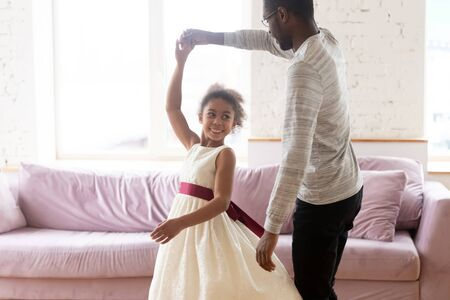 Loving african american father holding hand of adorable daughter dancing to favorite song at home. Diverse happy smiling dad teaching his young girl and twisting cute little kid in living room.