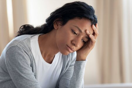 Sad and tired young african american girl hold her hand near head, feel sick or overworked, girl disappointed and crying alone, upset by bad news, problem and trouble, face close up Stockfoto