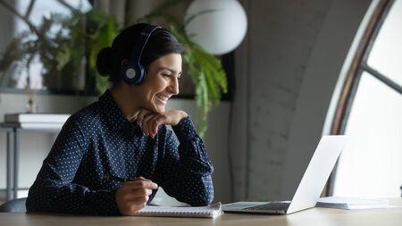 Une employée indienne souriante dans des écouteurs sans fil parle lors d'un appel vidéo, a une conférence Web avec des collègues, une travailleuse ethnique heureuse dans un casque regarde un webinaire sur un ordinateur portable moderne à la maison