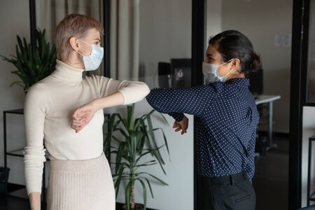 Smiling diverse female colleagues wearing protective face masks greeting bumping elbows at workplace, happy coworkers in medical facial covers protect from COVID-19 pandemics, healthcare concept