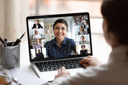 La mujer se sienta en el escritorio mirando la pantalla del ordenador donde el collage de gente diversa ve la webcam. Mujer joven de etnia india plomo videollamada chat distante, grupo de diferentes compañeros mediante la aplicación de videoconferencia