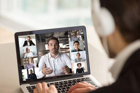 Diferentes edades y etnias diversos empresarios que participan en videollamadas grupales, vista de cámara web de pantalla de computadora portátil sobre el hombre en el hombro de los auriculares. Concepto de actividad de videoconferencia de comunicación distante