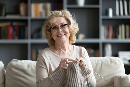Elderly woman in glasses sit on couch at home smile look at camera holding knitting needles and yarn knits clothes for loved ones, favorite activity and pastime, retired tranquil carefree life concept