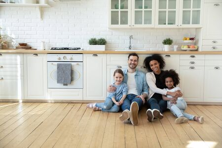 Portrait of happy multiracial young family with little kids sit on warm floor in design modern kitchen, smiling multiethnic parents with small biracial daughters relax in new renovated home together
