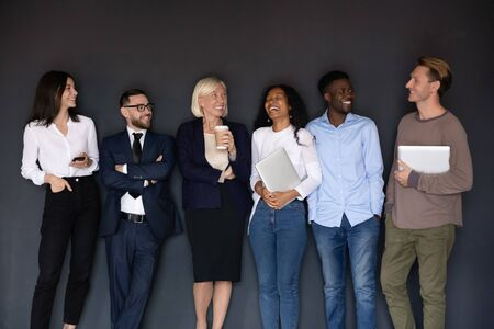 Overjoyed diverse multiethnic businesspeople stand posing near black wall have fun together joking at break, excited happy multiracial colleagues laugh and joke, unity, team spirit concept