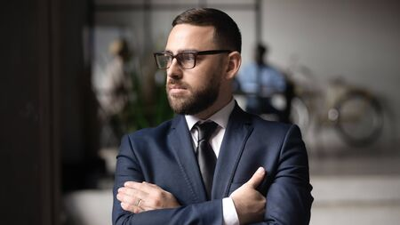 Serious Caucasian businessman in glasses look in distance thinking or visualizing, thoughtful middle-aged male boss lost in thoughts pondering over problem solution, plan, business vision concept