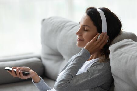 Calm satisfied woman in headphones enjoying favorite song close up, holding phone in hand, relaxing on cozy sofa at home, lazy weekend, beautiful young female with closed eyes listening music