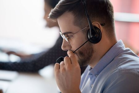 Close up call center worker side view face touch mic chatting with client use microphone give support help online, telemarketing occupation selling distantly services and products to customers concept