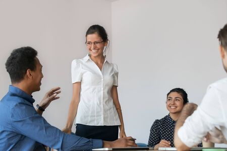 Mixed race businessman talk with cheerful presenter or female business coach during corporate educational training, friendly trainer listens question from participant african ethnicity company member