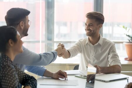 Businessmen gather in board room get acquainted shaking hands at meeting in office, company boss greeting corporate client, after discussion making deal celebrating each other with handshake concept