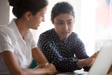 Diverse businesswomen discuss analyse online project look at laptop screen colleagues brainstorming strategizing together, mentor helping apprentice explain corporate program, support teamwork concept Foto de archivo