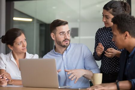 Multi-ethnic professionals colleagues gather together discuss startup ideas, diverse associates listening team leader or mentor give instructions analyzing results of work, teamwork brainstorm concept